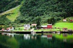 Casas de madera coloreadas en Noruega que refleja en el agua Foto de archivo libre de regalías