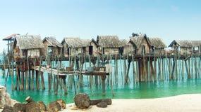 Casas de madera construidas a través de la línea de la playa Imagen de archivo libre de regalías