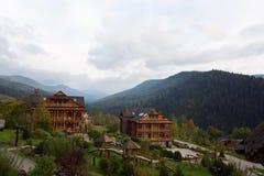 Casas de madera del vintage en centro turístico con los árboles de abedul, las hierbas del otoño y las plantas alrededor Alpain e Foto de archivo libre de regalías