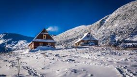 Casas de madera en montañas del invierno Imagen de archivo libre de regalías