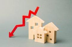 Casas de madera miniatura y una flecha roja abajo El concepto de propiedades inmobiliarias del bajo costo Tarifas más bajas del i fotografía de archivo libre de regalías