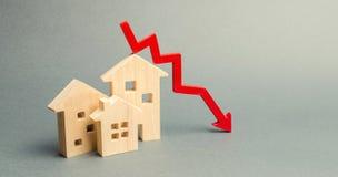 Casas de madera miniatura y una flecha roja abajo El concepto de propiedades inmobiliarias del bajo costo Tarifas m?s bajas del i imagen de archivo