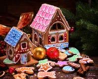 Casas de Navidad del pan de jengibre con el tejado colorido en la tabla de madera Imagen de archivo