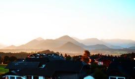 Casas de niebla de la salida del sol de la mañana con las sales en las colinas de las montañas en Austria Fotos de archivo