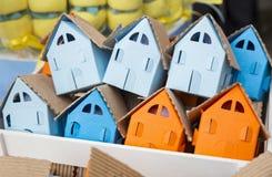 Casas de papel em cores diferentes, laranja, azul, ciana dentro do quadro de madeira fotos de stock royalty free