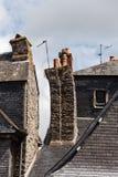 Casas de piedra viejas con las chimeneas y los azulejos de la pizarra Foto de archivo libre de regalías