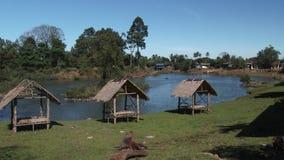 Casas de planta baja con una opinión sobre el río en Tad Lo, Laos almacen de metraje de vídeo