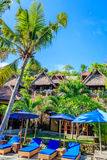 Casas de planta baja de madera y sunloungers azules con los paraguas, Nusa Lembongan, Indonesia imagen de archivo