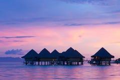 Casas de planta baja en la puesta del sol en Bora Bora Foto de archivo