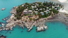 Casas de planta baja en orilla áspera cerca del mar Muchas cabañas tropicales establecidas en costa áspera cerca del mar tranquil almacen de video