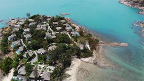 Casas de planta baja en orilla áspera cerca del mar Muchas cabañas tropicales establecidas en costa áspera cerca del mar tranquil almacen de metraje de vídeo