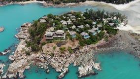 Casas de planta baja en orilla áspera cerca del mar Muchas cabañas tropicales establecidas en costa áspera cerca del mar tranquil metrajes