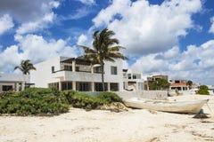Casas de praia mexicanas com barco e grama do mar sob o céu azul brilhante com nuvens fotos de stock