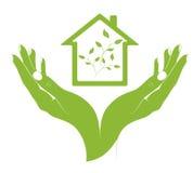 Casas de um eco do símbolo nas mãos fêmeas. Imagem de Stock