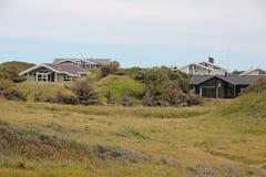 Casas de verano en colinas de la hierba verde con el cielo azul Imagen de archivo
