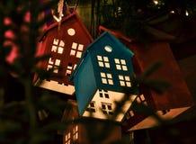 Casas del juguete que brillan intensamente en el árbol de navidad Fotos de archivo libres de regalías