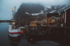 Casas del rorbu de Noruega y un barco de pesca en las rocas de las montañas del fondo sobre la opinión escandinava del viaje del  fotografía de archivo libre de regalías