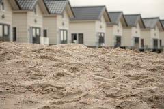 Casas detrás de la arena en la playa Imagen de archivo libre de regalías