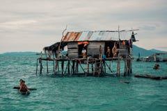 Casas do pernas de pau em uma vila aciganada do mar do bajau ao lado de um afloramento de rocha pequeno da ilha imagem de stock
