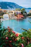 Casas do sul coloridas bonitas e baía azul do mar Mediterrâneo com algumas flores do vermelho no primeiro plano Vila de Assos Foto de Stock