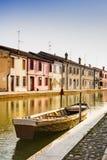 Casas e barco no canal de Comacchio, Itália imagem de stock