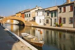 Casas e barco no canal de Comacchio, It?lia imagem de stock