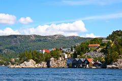 Casas e cabanas na costa do fiorde de Bergen. Imagens de Stock
