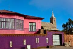 Casas e iglesia brillantemente coloreadas Foto de archivo libre de regalías