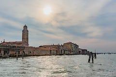 Casas e torre Venetian pela água sob o sol em Veneza, Itália fotografia de stock