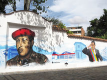 Casas em uma rua de Caracas com grafittis do presidente Chavez imagens de stock