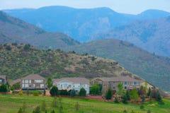 Casas en una ladera con los picos de montaña y la hierba verde Fotos de archivo libres de regalías