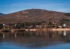 Casas entre los árboles delante de un lago fotos de archivo