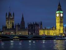 Casas iluminadas con focos de Big Ben (luz verde) del puente de Westminster del parlamento en la noche Fotografía de archivo