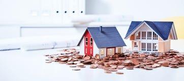 Casas miniatura entre monedas imagenes de archivo