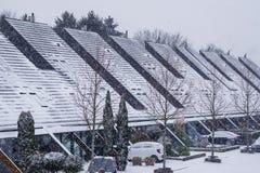 Casas modernas com telhados pointy em uma vizinhança holandesa durante a estação do inverno, tempo nevado em uma vila dos Países  fotos de stock