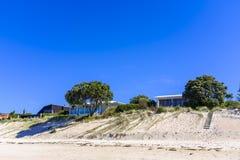 Casas modernas por uma praia imagens de stock
