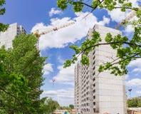 Casas multi de la historia bajo construcción a través de ramas de árboles imagen de archivo