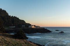 Casas na borda de um penhasco no por do sol em uma angra do Oceano Pacífico na costa de Oregon, EUA foto de stock