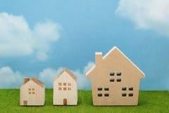 Casas na grama verde sobre o céu azul e as nuvens fotografia de stock royalty free