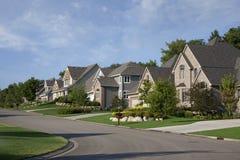 Casas na rua suburbana de gama alta na luz solar da manhã fotografia de stock