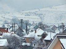 Casas nevado com as montanhas no fundo Imagem de Stock Royalty Free