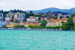 Casas no lago Lugano e montanhas em Ticino de Suíça Fotografia de Stock