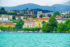 Casas no lago Lugano e montanhas em Ticino em Suíça Fotografia de Stock