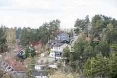 Casas nos montes cercados pelas árvores na vila de Holmlia, Noruega Imagens de Stock Royalty Free