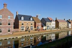 Casas novas da construção por um canal Fotos de Stock Royalty Free
