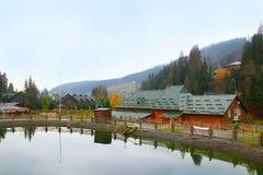 Casas pitorescas do lago e do turista no esqui ucraniano Bukovel Paisagem com o lago da montanha na estância turística Foto de Stock