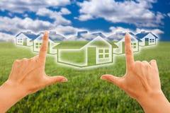 Casas que enmarcan de las manos femeninas sobre hierba y el cielo Fotografía de archivo libre de regalías