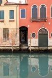 Casas que refletem no canal estreito em Veneza, Itália foto de stock royalty free