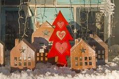 Casas rojas de madera del árbol de navidad y del juguete en escaparate de la tienda Imagen de archivo libre de regalías