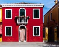 Casas rojas y amarillas en la isla colorida de Burano, Venecia, foto de archivo